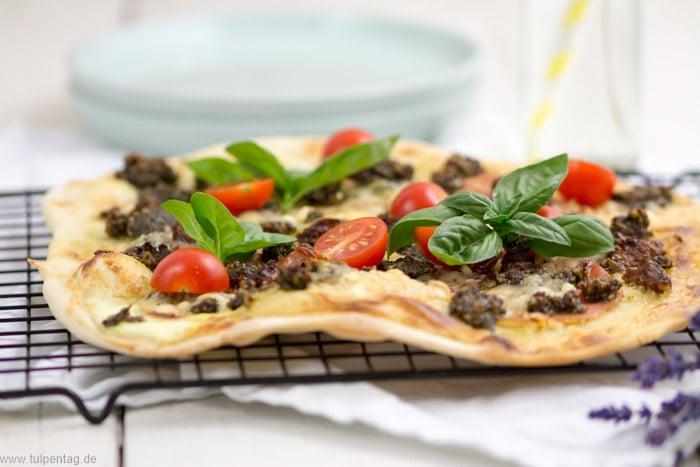 Flammkuchen mit Serranoschinken, Pesto, getrockneten und frischen Tomaten, Basilikum und Parmesan.