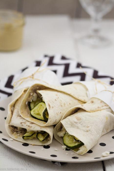 Vegetarische Tortilla-Wraps mit Zucchini, Hummus und Feta. Schnell und einfach zu machen.